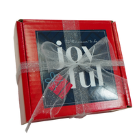 Red box with navy blue card saying Tis The Season To Be Joyful. Red box is wrapped in a glittery silver ribbon with a bow.