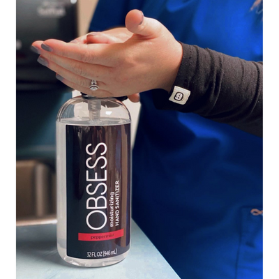 Nurse wearing blue uniform with black sleeves using the OBSESS peppermint 32 oz hand sanitizer.
