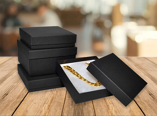 Stack of 3 Black Cotton Filled Boxes with 1 Open Black Box with a Gold Chain All on a Wood Table