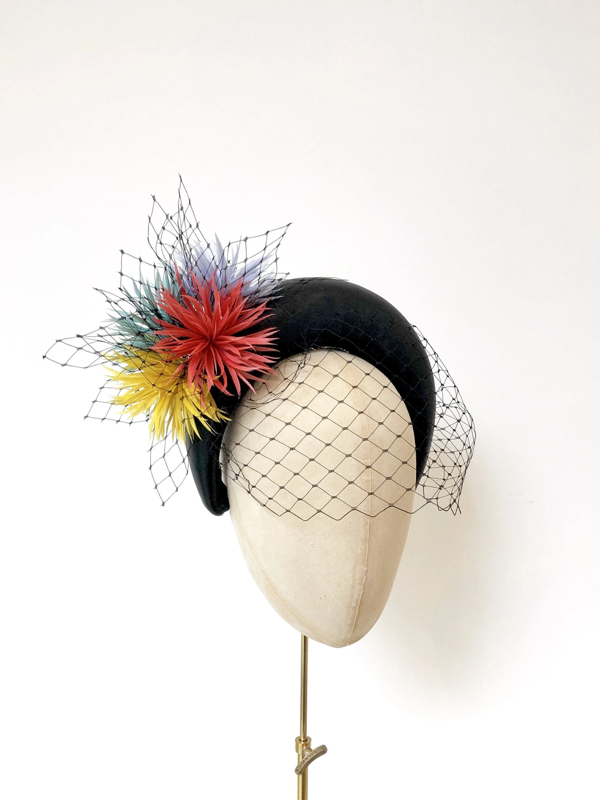 black leather padded halo crown headband, with coral, yellow, green and blue spikey feather flowers and black widow veiling