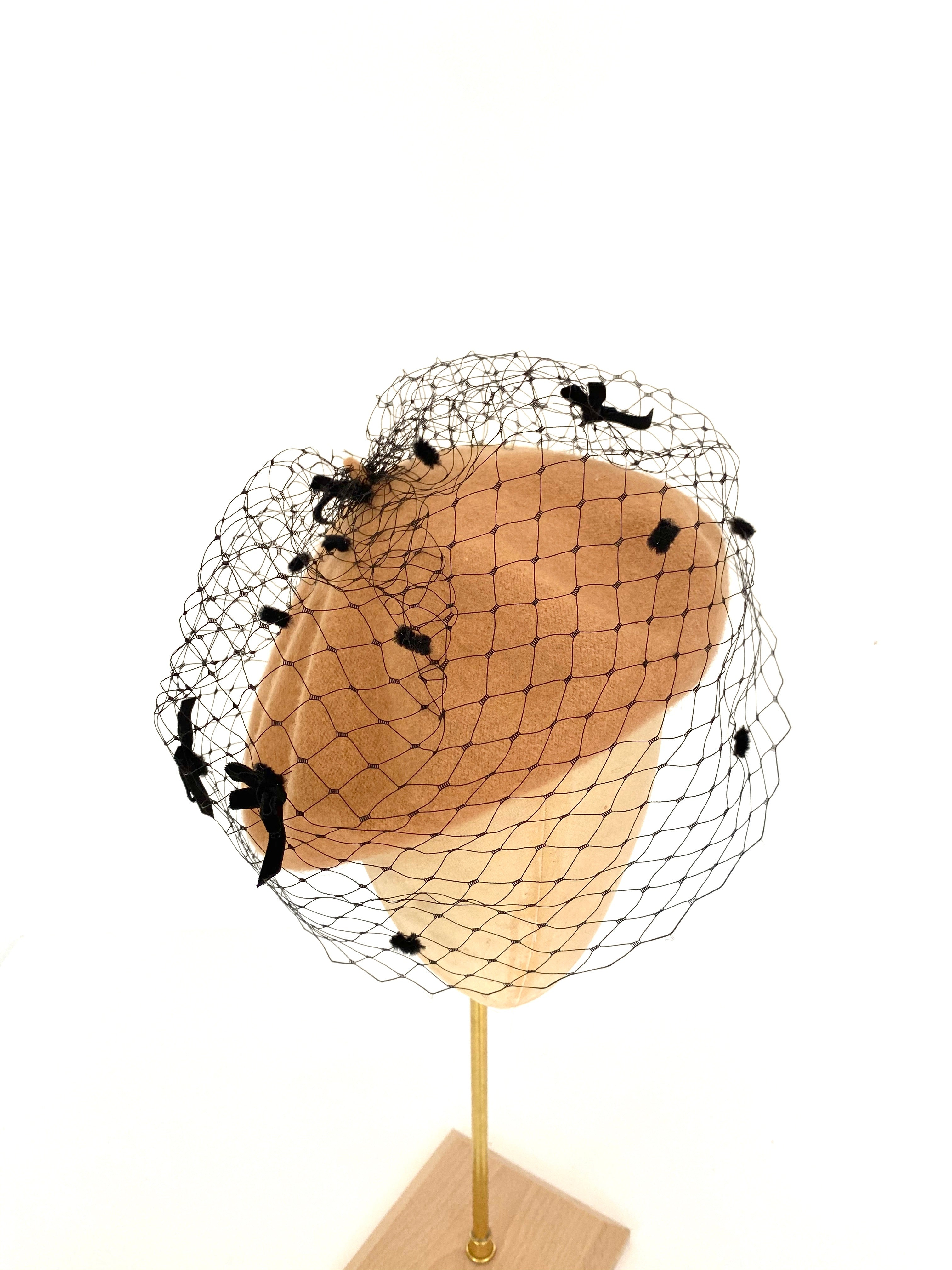 beige beret with black veiling and velvet bows