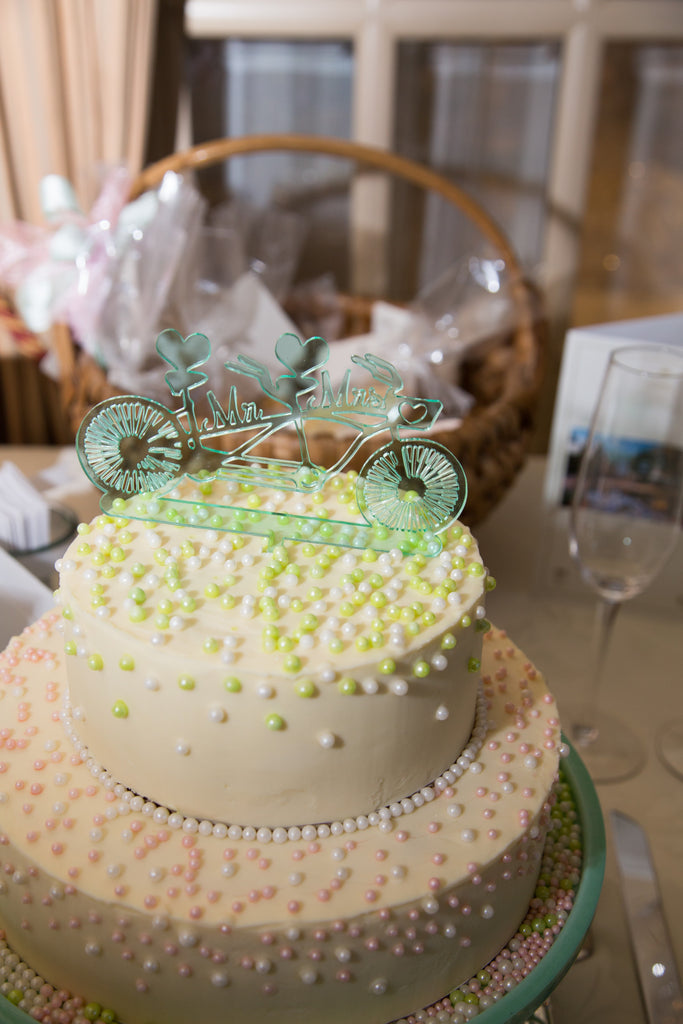 White wedding cake with pale green, tandem bicycle wedding cake topper that says, Mr. and Mrs. at the Chateau Vaudreuil reception venue in Montreal, Quebec.