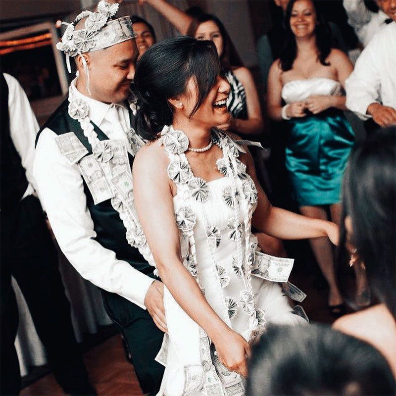Filipino newlyweds in the middle of their money dance, looking festive in a crown, sash, and garlands made of cash.