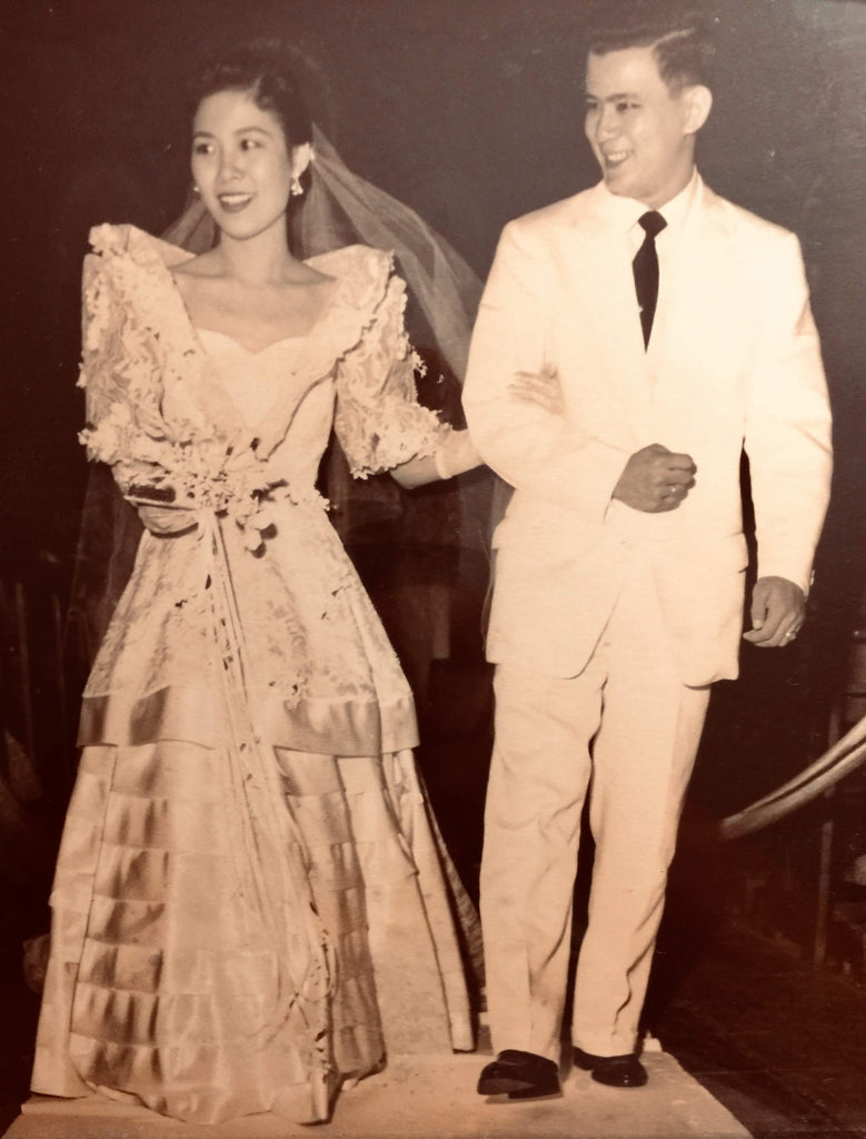 Bride in a traditional Filipiniana terno wedding gown with a groom dressed in a white suit in the Philippines.