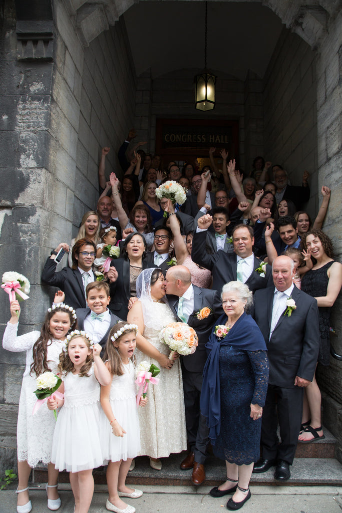 A Filipino and Italian couple are surrounded by their friends and family at the church outside of their small and intimate wedding in Montreal.
