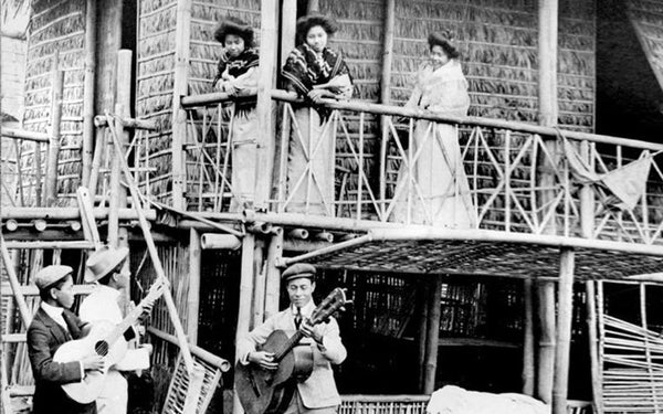 A young man together with friends practicing the harana, or the serenading of a maiden below her balcony.