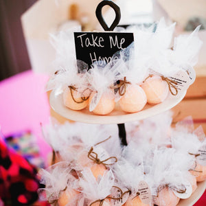 "Mini orange handmade bath bomb product favors displayed on a two tiered stand with the sign ""take me home"" on top"