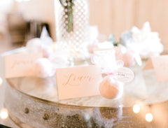 light pink bath bomb favors scattered across a glass table with name tags