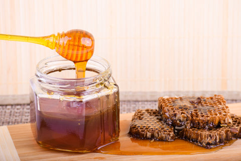 raw honey dripping from jar