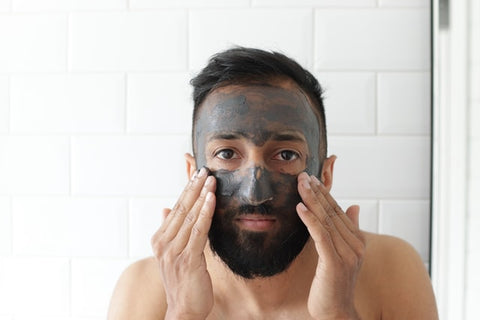 man with charcoal face mask