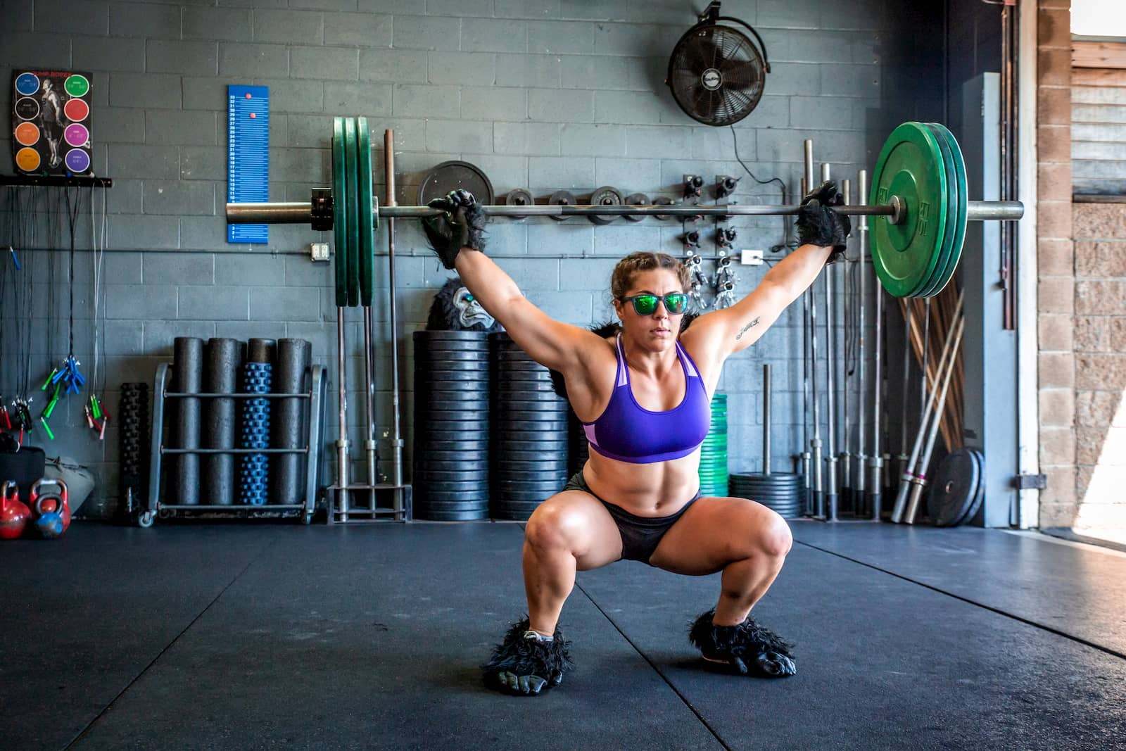 Woman with gorilla gloves squats in goodr gray sunglasses