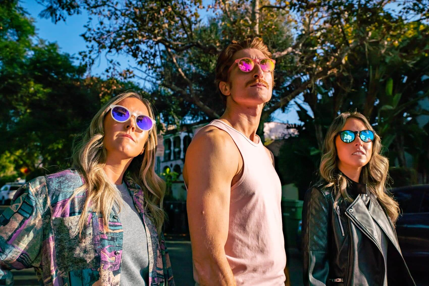 round mirrored hipster sunglasses by goodr being worn by a man and two women