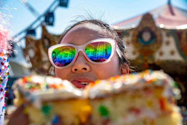 rainbow polarized sunglasses on woman eating rainbow cake