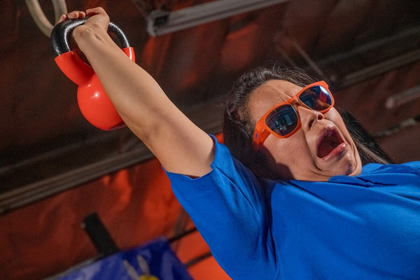 Girl wearing goodr orange sunglasses with blue lenses and blue shirt working out with orange kettlebell