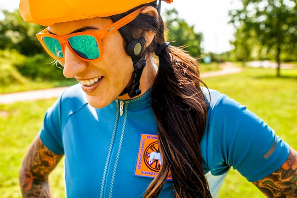 Woman on bike with orange polarized sunglasses and an orange helmet