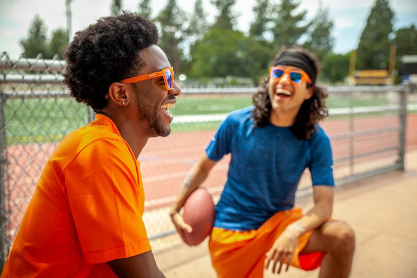 Two men chatting while wearing goodr orange sunglasses and playing football