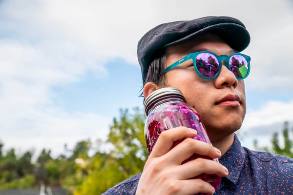 hipster man wearing teal sunglasses while pickling