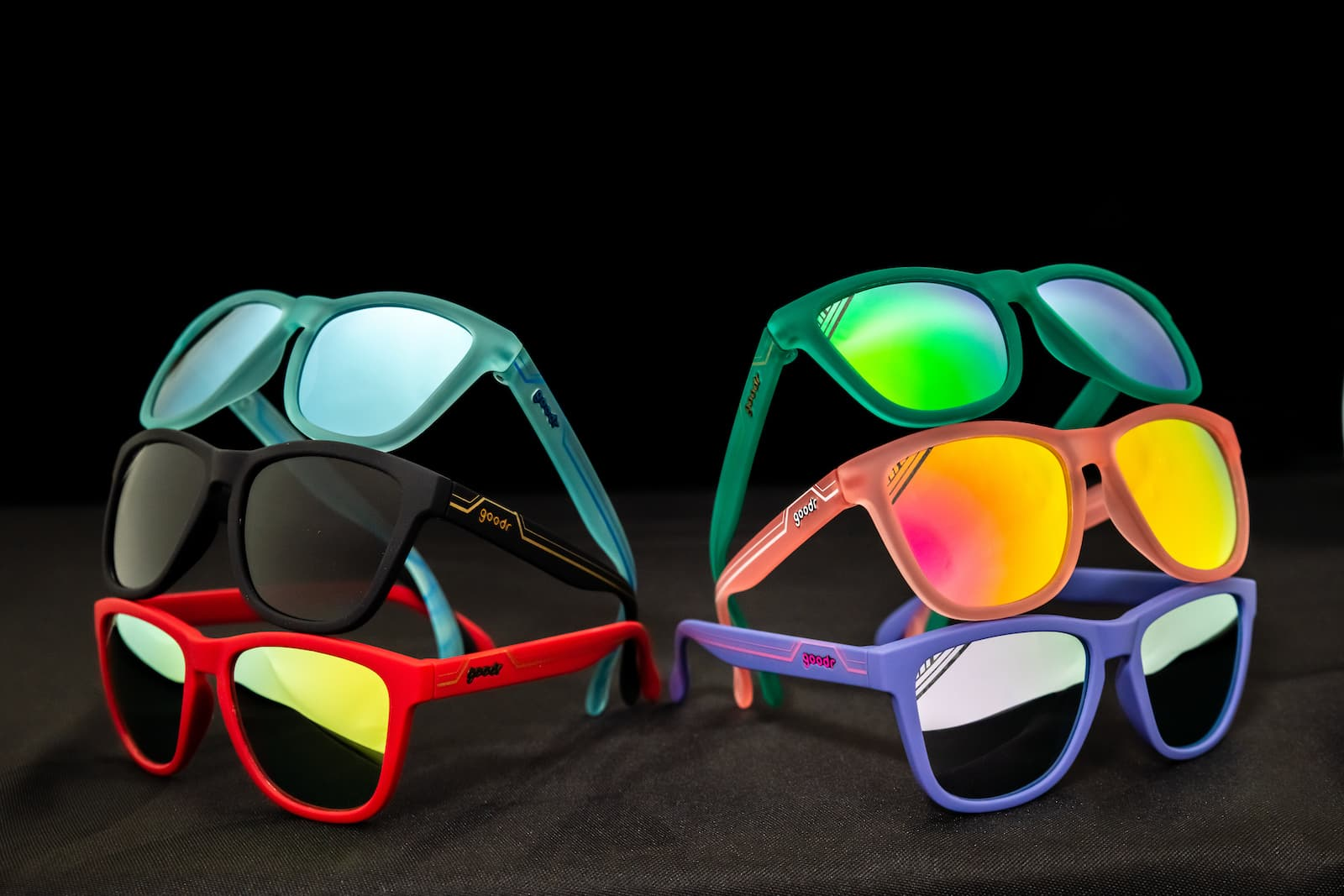 Six goodr sunglasses with Art Deco detailing - colored frames in light blue, green, black, red, peach, and purple