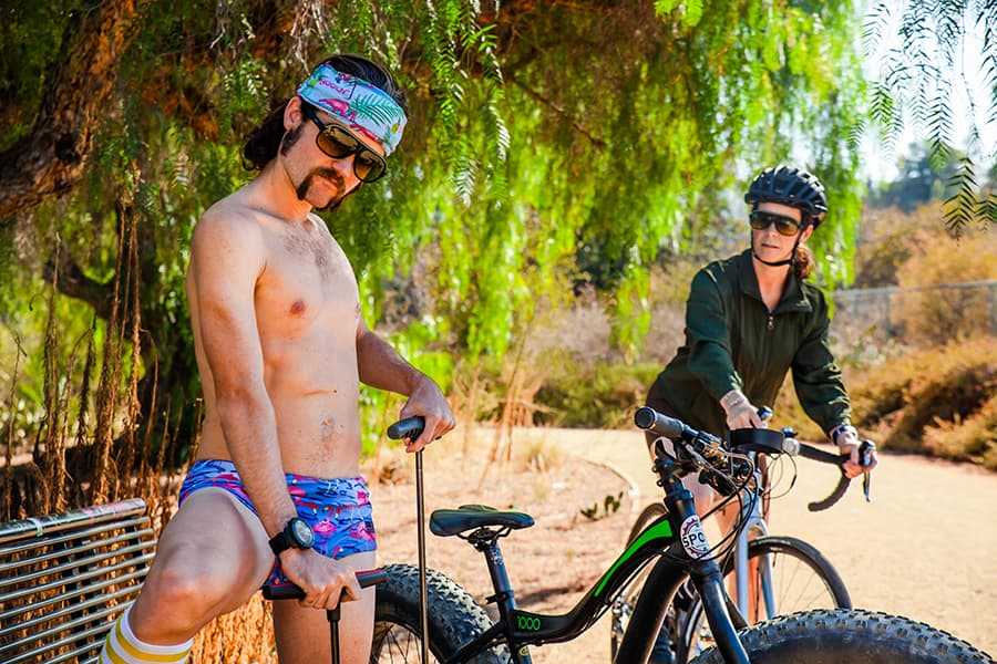 black cycling sunglasses on man and woman on bikes
