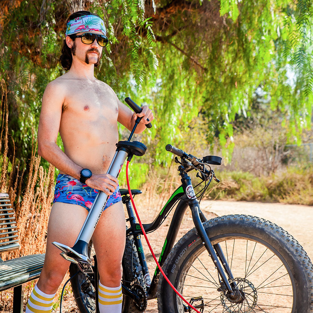 Man with bike pump wearing Goodr Dirk's Inflation Station sunglasses