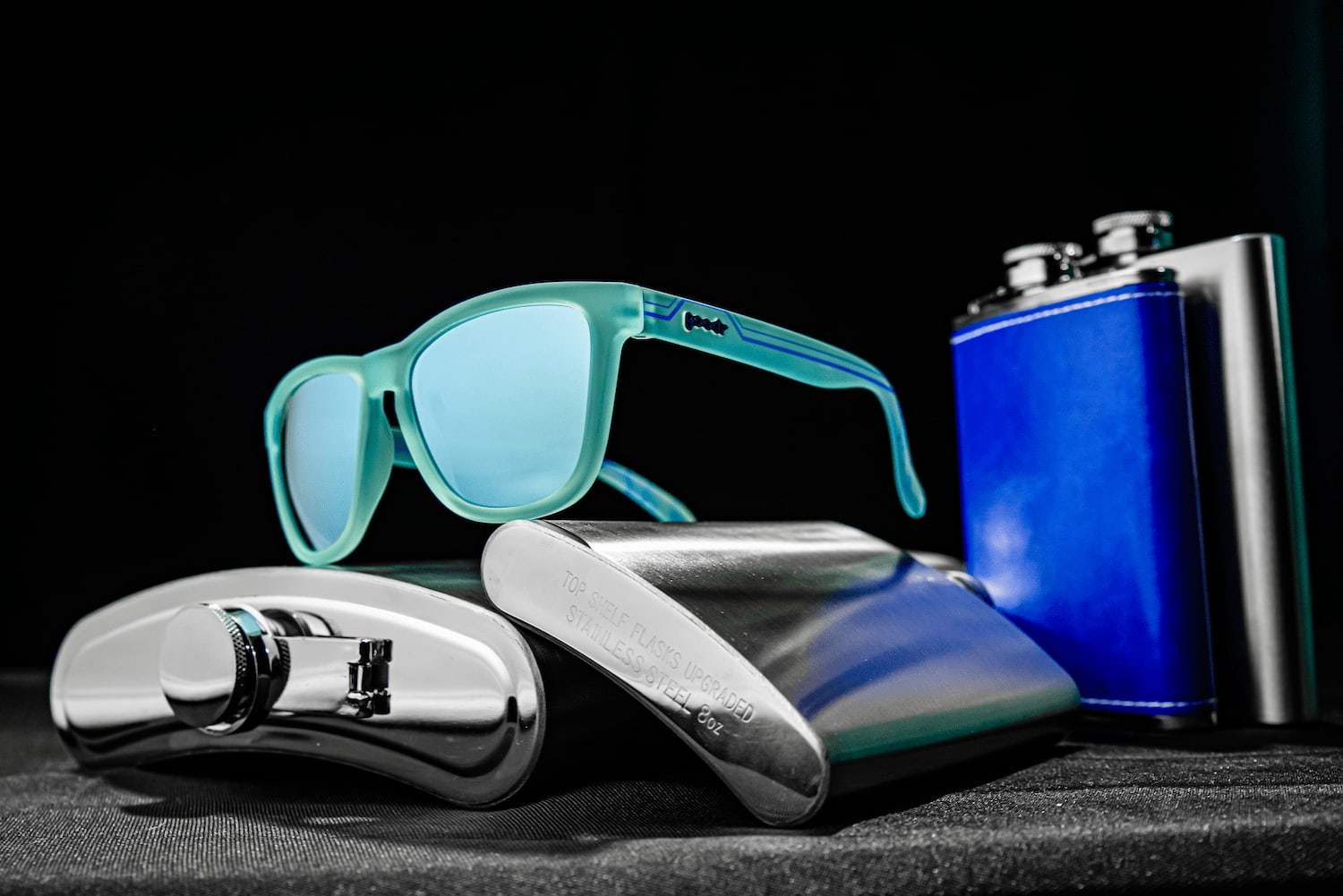 goodr light blue sunglasses resting on flasks