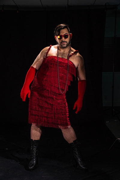 Man wearing a roarin' 20's style fringe dress and red gloves and red framed goodr glasses
