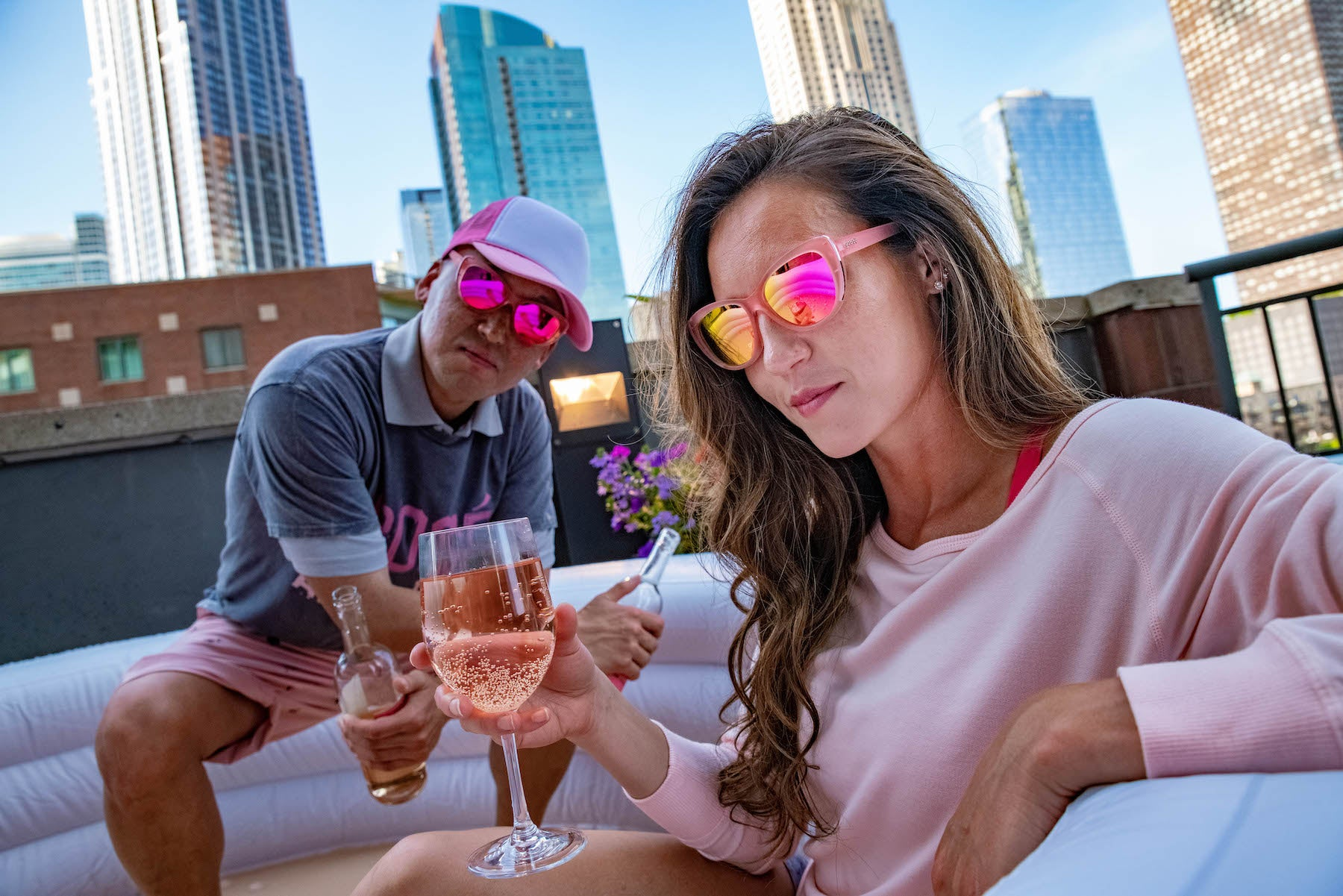 pink cateye sunglasses on man and woman drinking rose