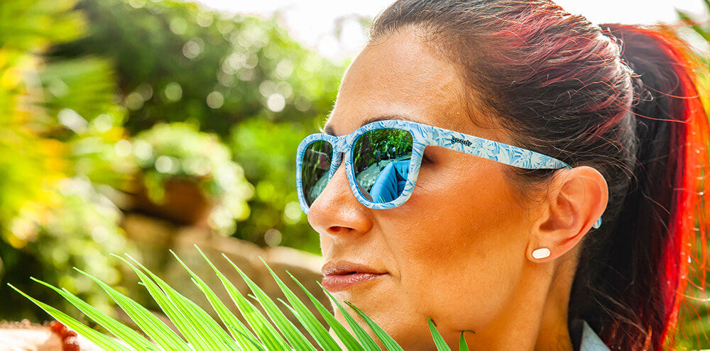 Lady wearing blue frames with all over palm leaf print and blue lens sunglasses with polarized, uv protection, and reflective lenses