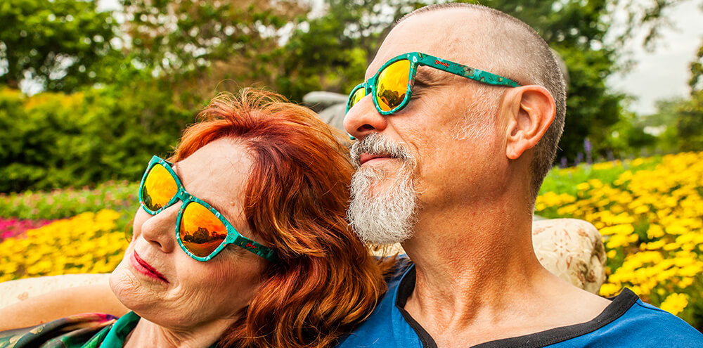 Old couple wearing green framed sunglasses with all over flower print and polarized burnt orange UV protection mirrored lenses