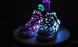 GloKix showing black pair of light up shoes glowing purple and blue on a turn table