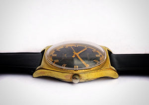 Side view of Gold and black vintage luxury dive watch with stick hands and sweep seconds made by Bulova