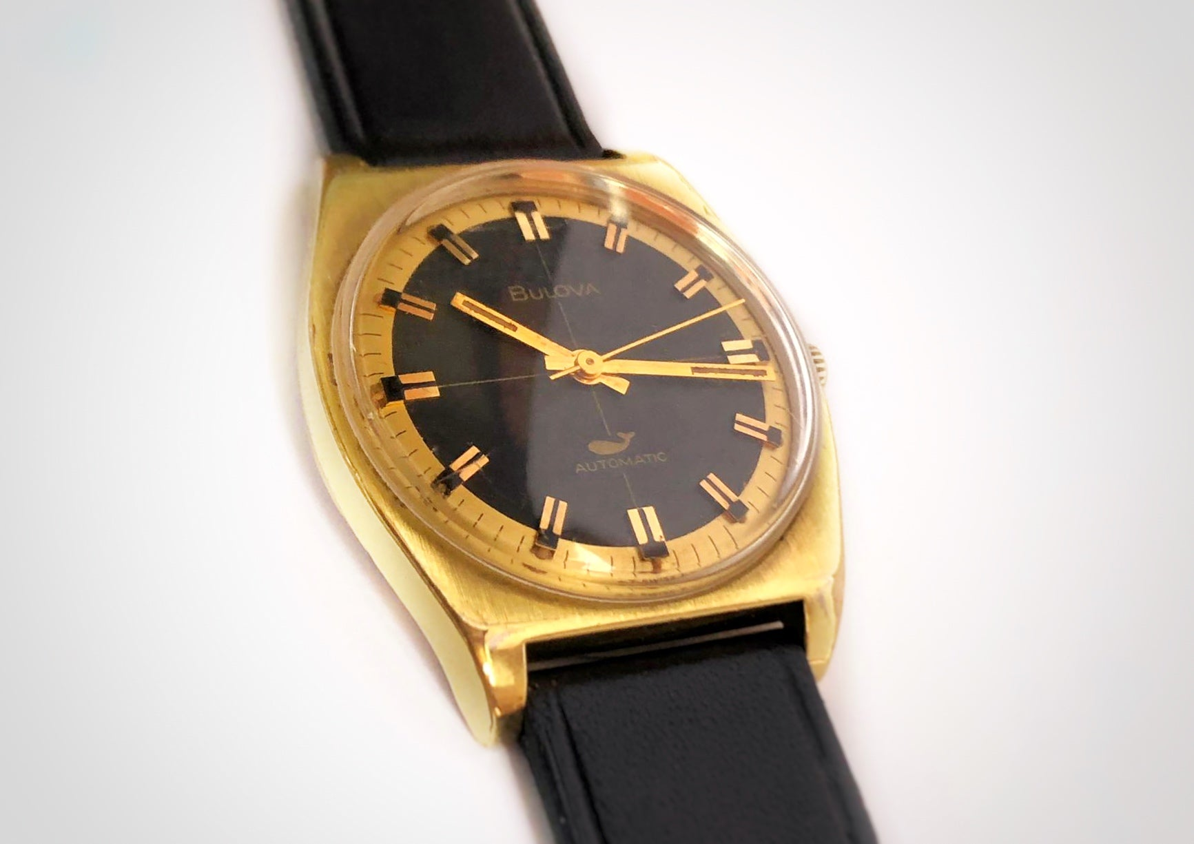 Three quarters view of Gold and black vintage luxury dive watch with stick hands and sweep seconds made by Bulova
