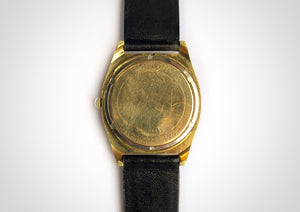 Back of Gold and black vintage luxury dive watch with stick hands and sweep seconds made by Bulova, including caseback with writing on it