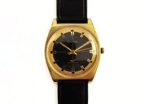 Gold and black vintage luxury dive watch with stick hands and sweep seconds made by Bulova