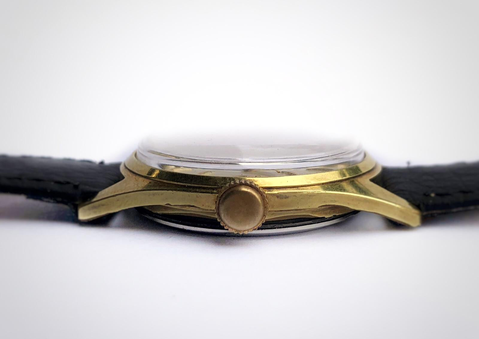 Side view of Vintage watch with linen dial and 3-6-9 pattern and gold case made by Gruen. First watch worn by James Bond as Sean Connery
