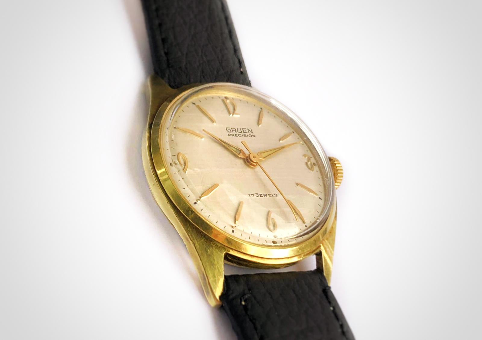 Three quarters view of Vintage watch with linen dial and 3-6-9 pattern and gold case made by Gruen. First watch worn by James Bond as Sean Connery