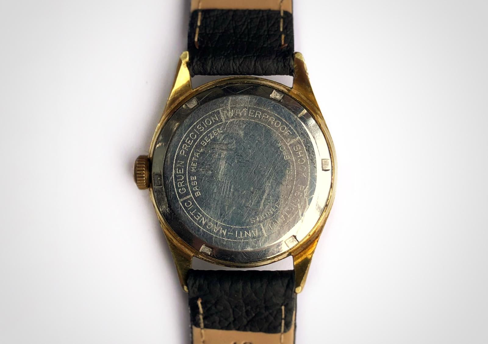 Back of Vintage watch with linen dial and 3-6-9 pattern and gold case made by Gruen. First watch worn by James Bond as Sean Connery with engraving on caseback