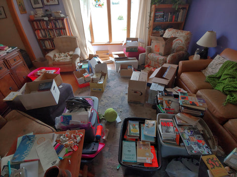 Living room littered with books in process