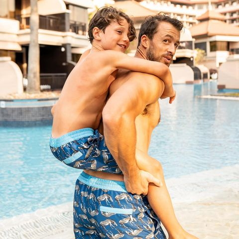 father and son in matching swim shorts in swiming pool
