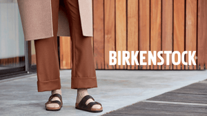 person standing in two strap brown leather sandals with word birkenstock logo in white