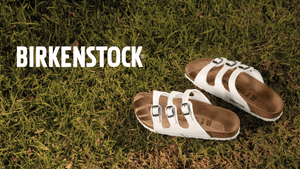 white three strap sandals laying in green grass with words birkenstock in white top left corner