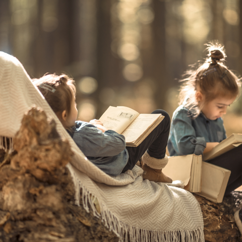 2 girls reading books in the woods