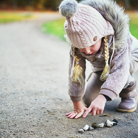 Girl pointing to stones and acorn on the path