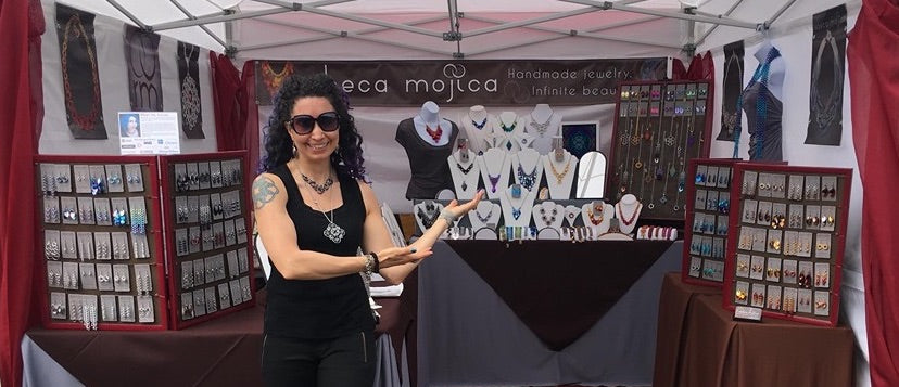 Rebeca Mojica showing off her craft show booth of chainmaille jewelry.