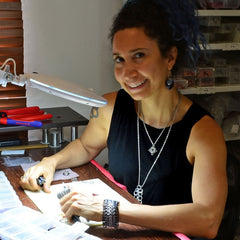jewelry artist rebeca mojica sitting at worktable holding pliers