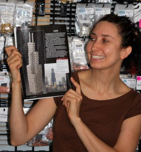 Photo of Rebeca Mojica holding up Art Jewelry magazine to the page in which her chainmaille sculpture It'll Always Be Sears To Me is shown.