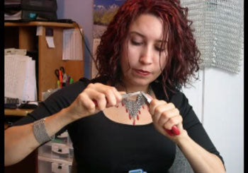 Rebeca Mojica is holding pliers and weaving chainmaille