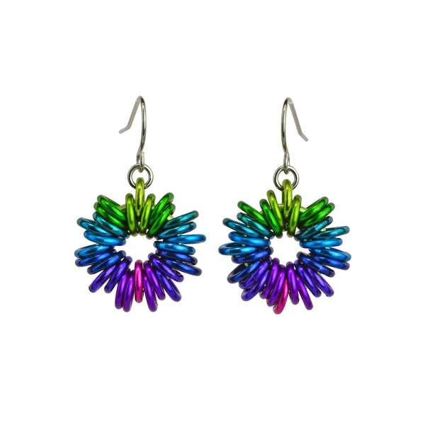 Electric Rainbow Coiled Earrings by Rebeca Mojica Jewelry. Each earring has 28 colorful jump rings added to a single large ring; the overall look resembles coiled wire.