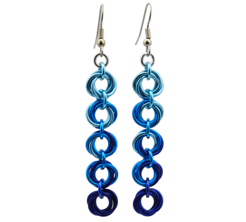 "Chainmaille earrings of 5 linked ""knots"" hanging from the earwire. Top knot is light blue, transitioning as you move down the earring to medium blue and dark blue. chainmaille earrings by Rebeca Mojica"