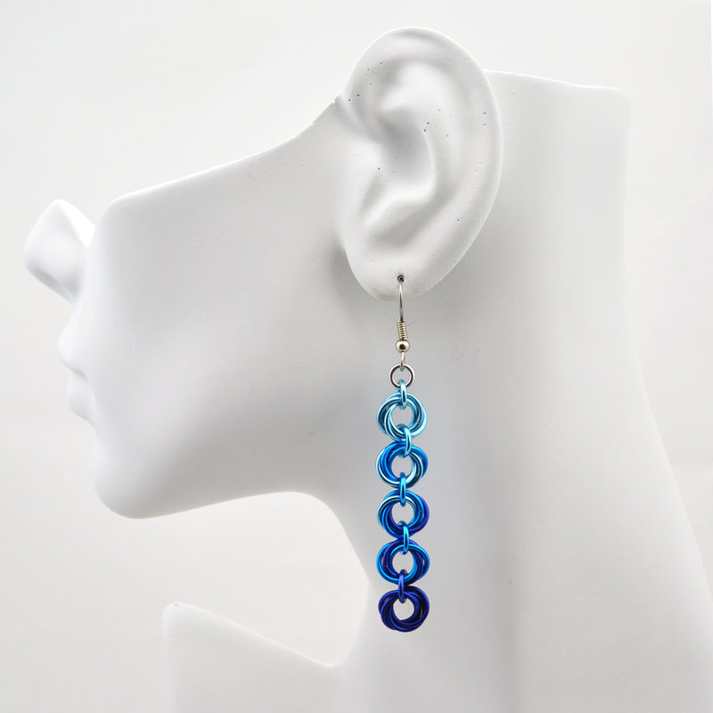 Closeup of chainmaille earrings on display head. Earrings are 5 knots linked vertically and transitioning from a top knot of light blue to a bottom knot of dark blue. Five Knot Earrings by Rebeca Mojica
